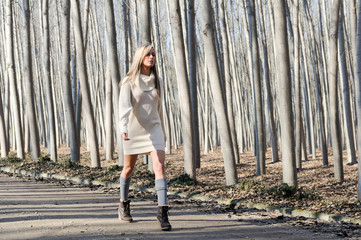 Beautiful blonde girl, dressed with beige dress, walking in a ru