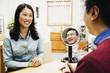 Asian optician assisting customer