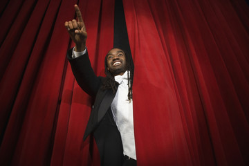 African man pointing through stage curtain
