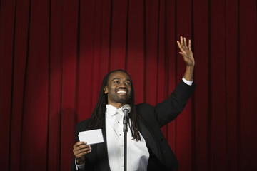 African man waving on stage