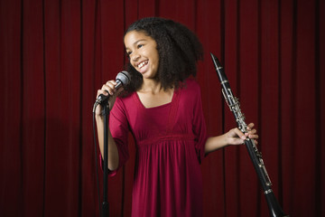 Mixed Race girl holding clarinet on stage