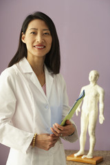 Asian female doctor next to Acupuncture model