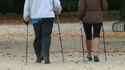 Nordic walking - active couple exercising outdoor