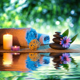 Fototapety two candles and towels black stones and purple daisy on water