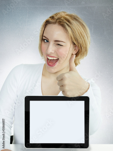 Business woman winking over her tablet pc with copyspace