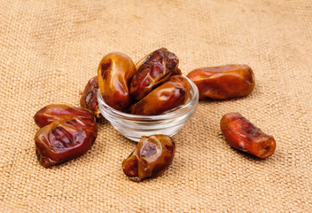 dried dates on glass bowl on canvas background