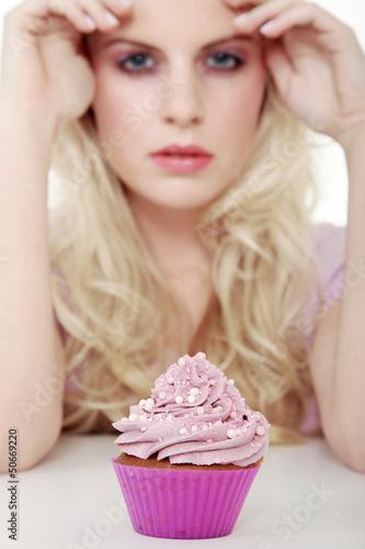 Junge hübsche Frau mit Cupcake blickt cool