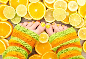 Female legs between citrus fruits