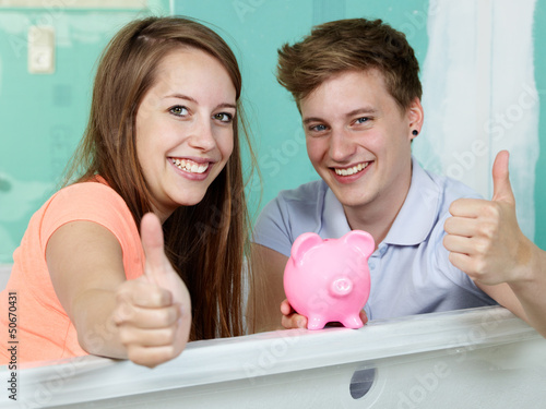 Couple sit in the bathtub of their site showing thumbs up