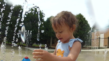 Cute little girl playing at water park