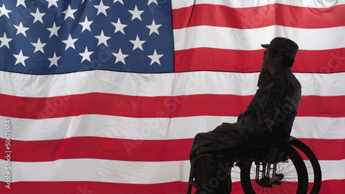 Silhouette of a soldier in a wheelchair in front of US flag