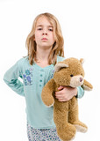 Angry kid in pajamas holding teddy bear