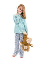 Tired little girl in pajamas holding teddy bear