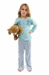 Angry girl holding teddy in pajamas