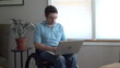 Man in wheelchair working on his laptop computer at home