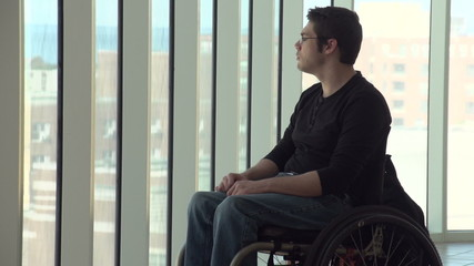 Man in wheelchair looking out a highrise window