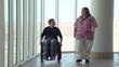 Man in wheelchair talking with nurse in hospital