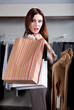 Woman carries paper packets with buyings