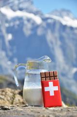 Swiss chocolate and jug of milk against mountain peak. Switzerla