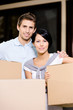 Couple carrying pasteboard packages while moving to new house