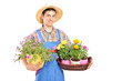 Male gardener with a straw hat holding flower plants