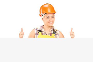 Young female with helmet posing behind a panel with thumbs up