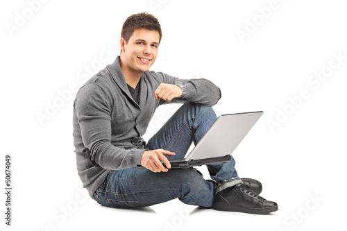 Handsome guy working on a laptop and sitting on a floor