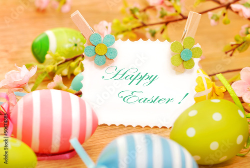 easter eggs and greetings card on wooden background