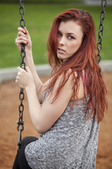 Young Woman with Beautiful Auburn Hair on a Swing