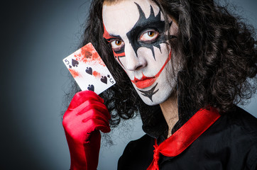 Evil clown with cards in dark room