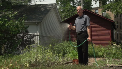 Man watering his backyard garden, slow motion shot