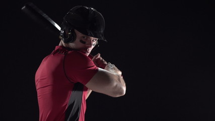 Baseball player swinging the bat, close up, black background