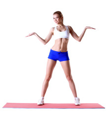 Cheerful slim woman posing on mat in studio