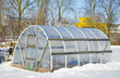 Leinwanddruck Bild - handmade polythene greenhouse for vegetable  in winter  on snow