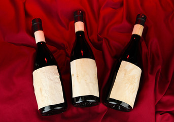 Wine bottles on red cloth background