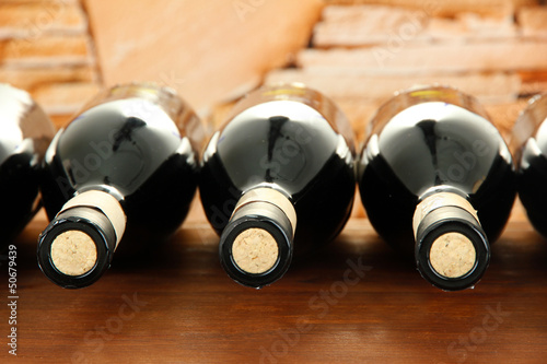 Wine bottles on wooden table, on stone background