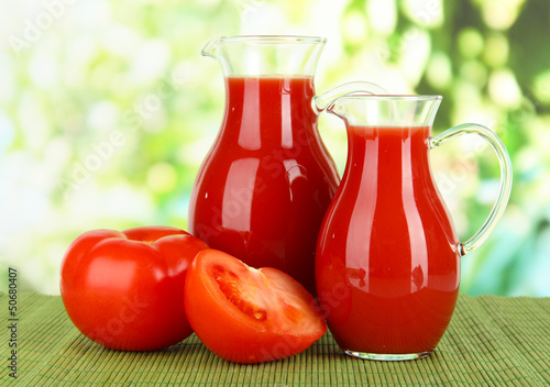 Tomato juice in pitchers on table on bright background