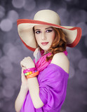 Beautiful red-haired girl in hat at bokeh background