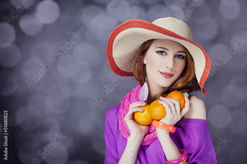Beautiful red-haired girl with oranges at bokeh background