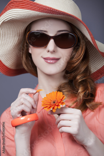 Beautiful red-haired girl in hat at white background