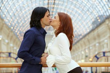 Young couple, kissing on bridge
