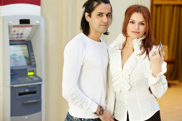 Dark-haired man and red-haired woman stand