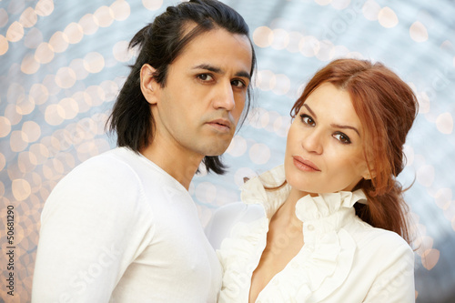 Dark-haired man and red-haired woman stand side by side and look
