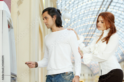 Dark-haired man with credit card and red-haired woman stand near