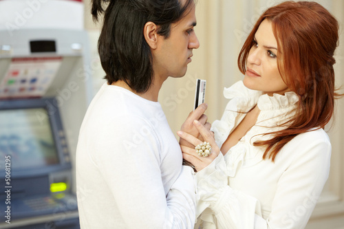 Dark-haired man with credit card in hand and red-haired woman
