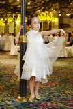 Little girl-model performs white gown, standing