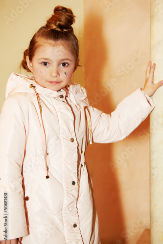 Girl in light coat stands, leaning one hand on marble pillar