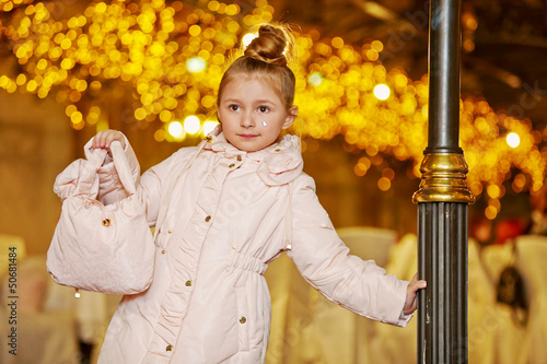 Girl in light coat stands, leaning one hand
