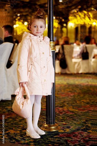 Girl in light coat stands near to  decorative lamp post