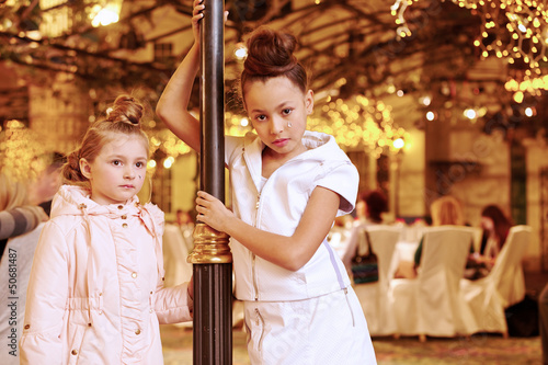 Girls stand near decorative lamp post, one in light coat